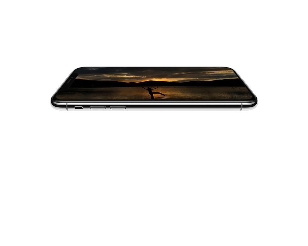 iPhone X シルバーの画面に夕闇の中、山々が見えるほとりのそばで、一人の人が踊っている写真が写っている画像
