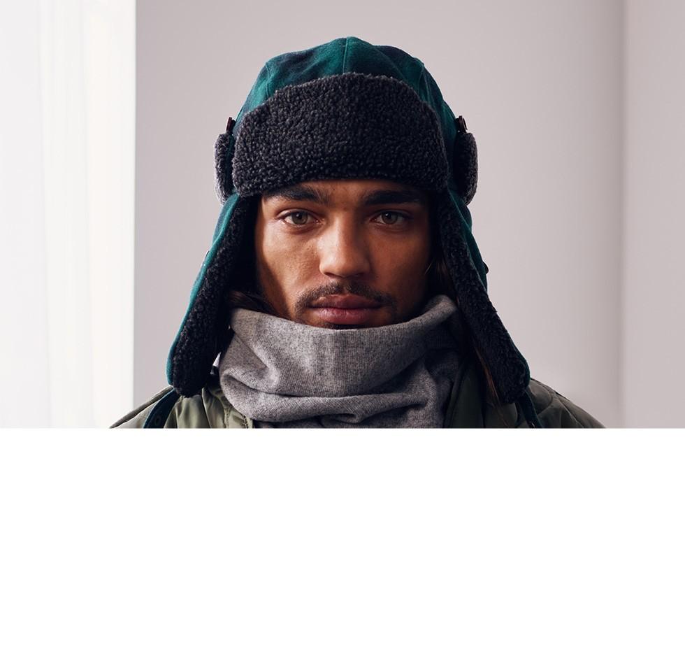 帽子をかぶり、マフラーを巻いてコートを着ている異国の青年男性の写真