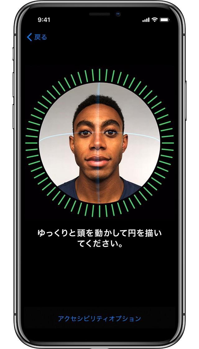 iPhone X シルバーの画面に、緑の枠の中に男性の顔が写っており、そこに緑のドッドのセンサーが反応している画像