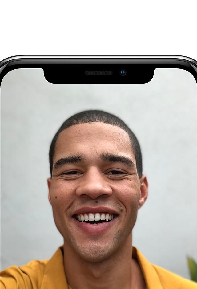 iPhone X シルバーのフロントカメラで一人の男性がとびきりの笑顔を向けている写真