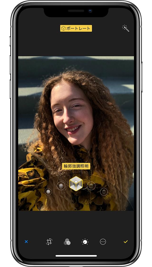 iPhone Xの新機能ポートレートライティングを使って、スタジオで撮ったような自分の写真を撮って楽しんでいる女性の写真