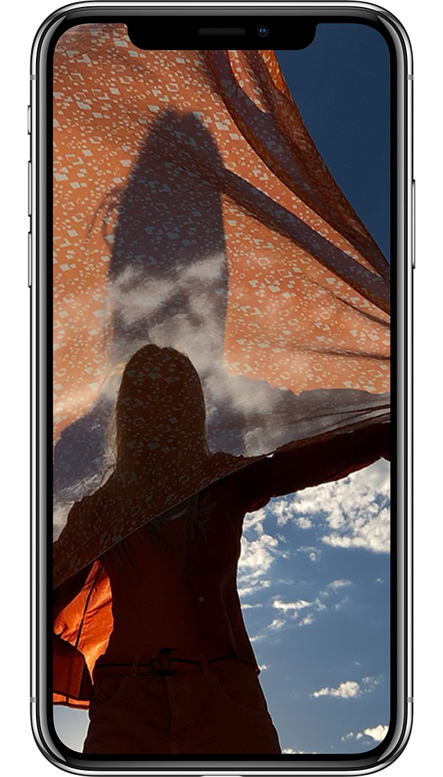 iPhone X シルバーの画面に日が落ちていく中、一人の女性のストールが風で美しくなびいている躍動感のある写真が写っている画像