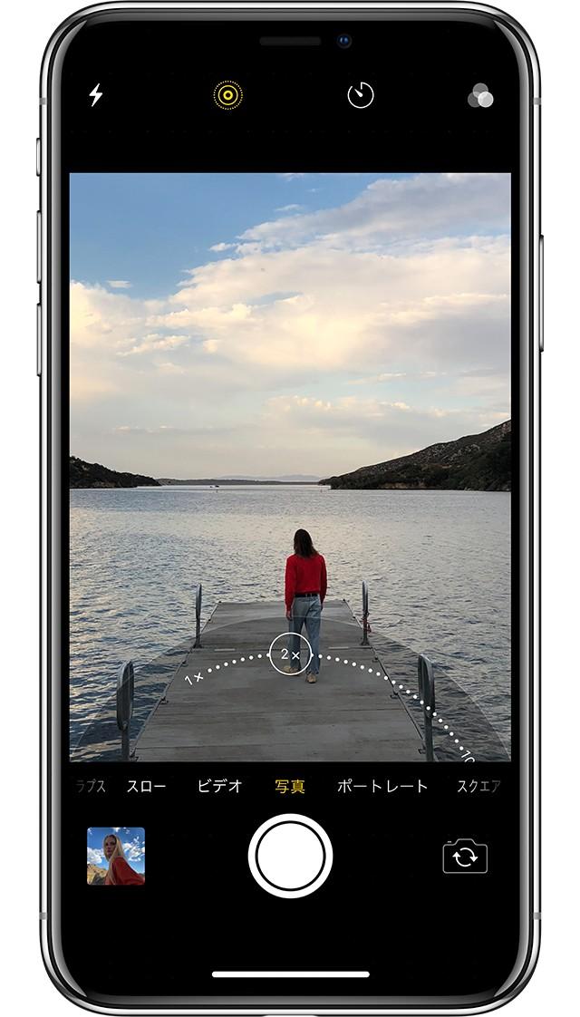 iPhone X シルバーの光学ズームを使って、夕方の桟橋を一人で歩く女性の後ろ姿を撮影しようとしている画像