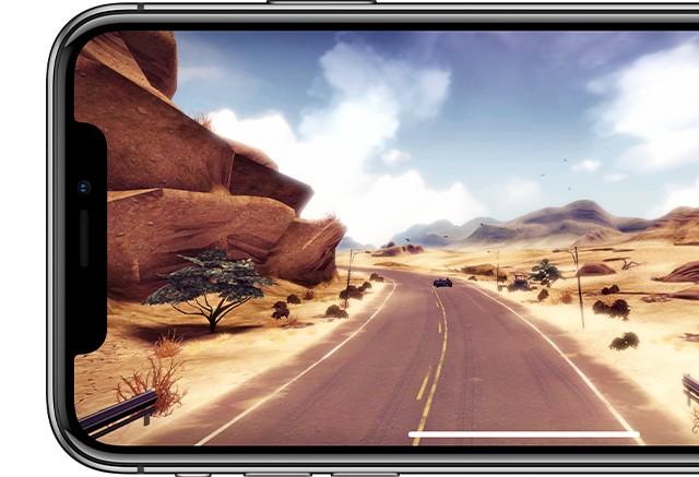 iPhone X シルバーの画面に砂漠の中のハイウェイを颯爽と駆け抜ける1台の車が写っている画像