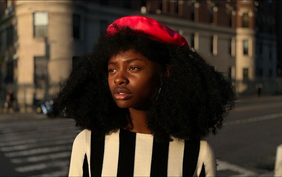 iPhone XS・iPhone XS Maxのデュアルカメラシステムで、街中の交差点で赤いベレー帽をかぶった黒髪スパイラルパーマの黒人女性を写しだした画像