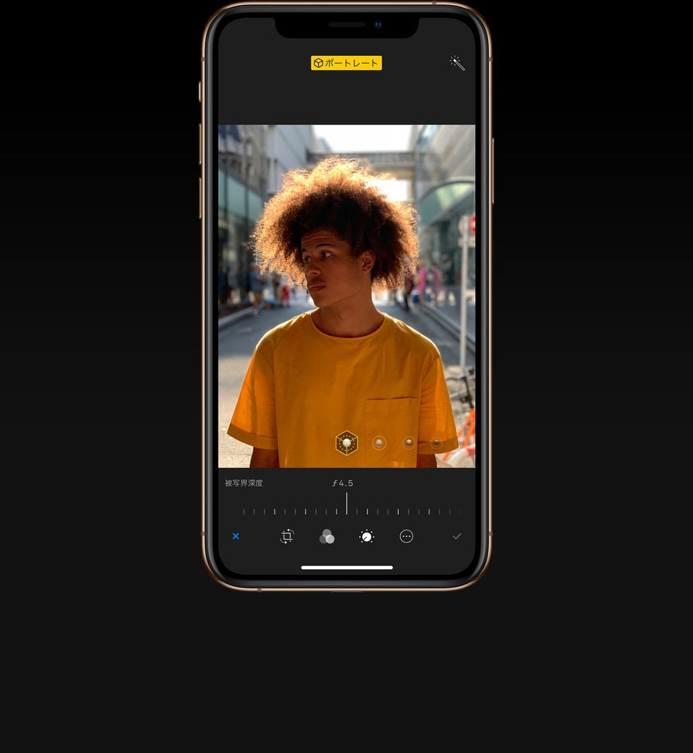 iPhone XS・iPhone XS Maxのデュアルカメラシステムの深度コントロールで、スパイラルパーマで黄色いTシャツを着た若い外国人男性を写した写真の被写界深度を調整している画像