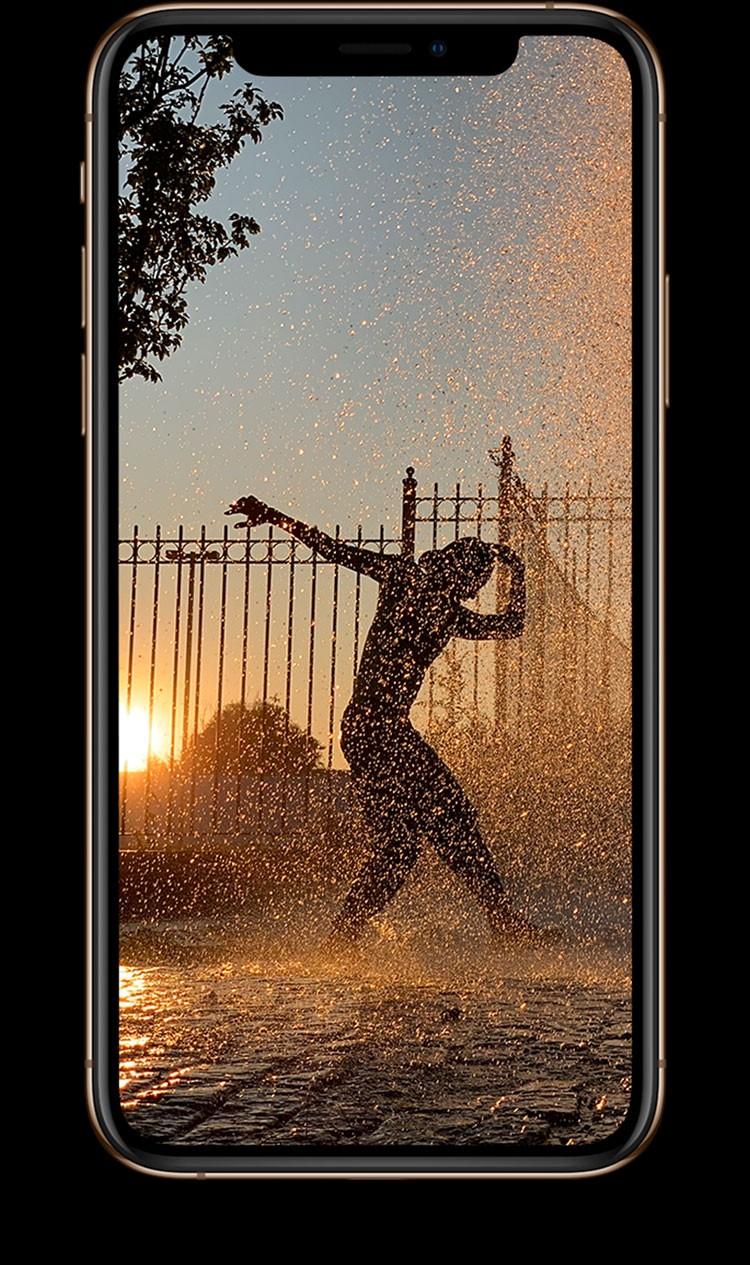 iPhone XS・iPhone XS Maxの画面に夕刻、夕日をバックに踊っている人の姿が写っいる画像