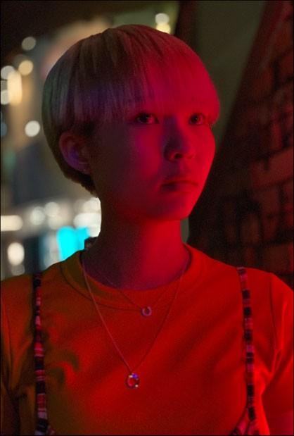 iPhone XS・iPhone XS Maxのデュアルカメラシステムのポートレードモードで、夜の街の背景をぼかし、前髪が眉毛の下でまっすぐ切り揃えられたベリーショートの女性、上半身を写しだした画像